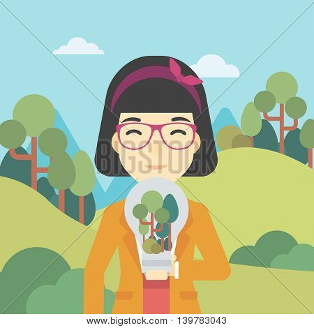 An asian woman standing on the background of green forest and holding in hands a big lightbulb with trees inside. Green energy concept. Vector flat design illustration. Square layout.