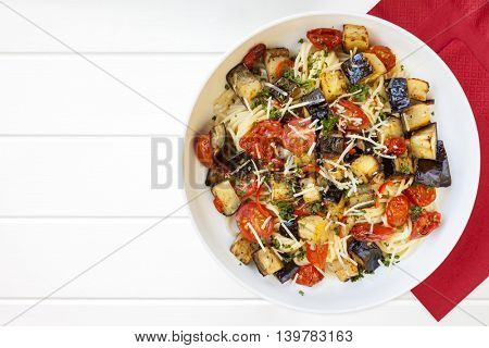 Spaghetti with roasted eggplant or aubergine and cherry tomatoes.  Top view.