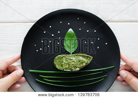 Mussel served with green herbs on black plate. Hand holding plate with seafood decorated in form of ship. Seafood meal serving, mediterranean cuisine