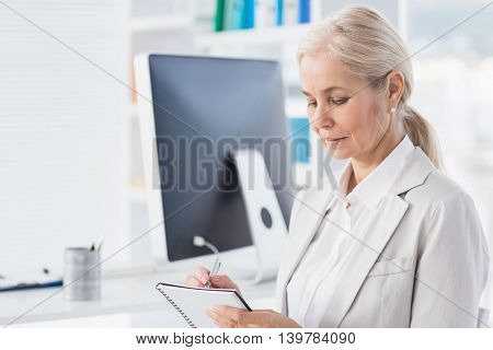 Focused female therapist writing notes in office