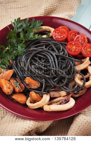 Black spaghetti pasta with mussels and squid rings