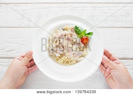 Plate with spaghetti carbonara serving, flat lay. Presentation of traditional Italian meal, white wooden background