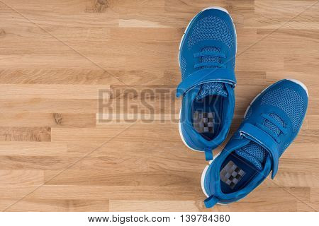 Blue Sneakers with wooden background.Blue Sneakers with wooden background