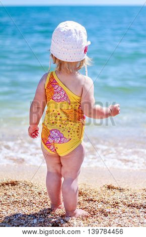 Baby Girl Playing On The Beach Near The Sea