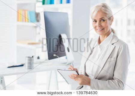 Portrait of smiling therapist holding notepad in office