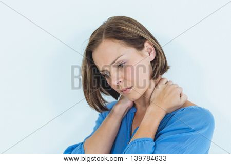 Thoughtful woman suffering from neck pain at home