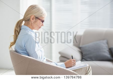 Focused therapist writing notes on sofa in office