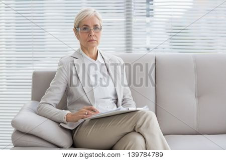 Portrait of therapist with notes sitting on sofa in ofice