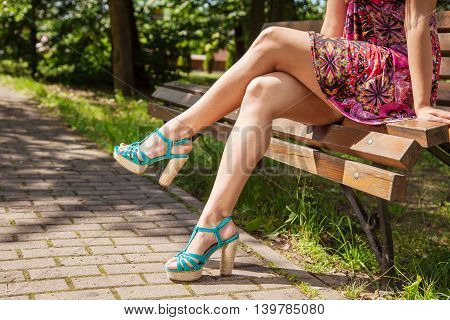 young girl in green shoes sitting on a park bench. legs closeup