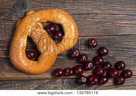 Tasty pretzel with poppy seeds and cherry on wooden background top view