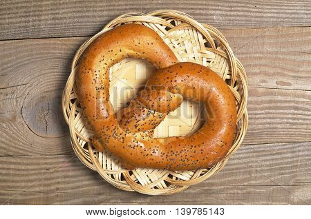 Delicious pretzel with poppy seeds in wicker plate on wooden table top view