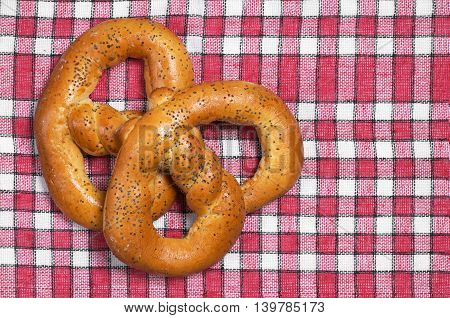 Homemade pretzels with poppy seeds on red tablecloth top view