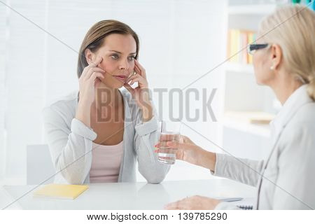 Therapist offering glass of water to young woman in office