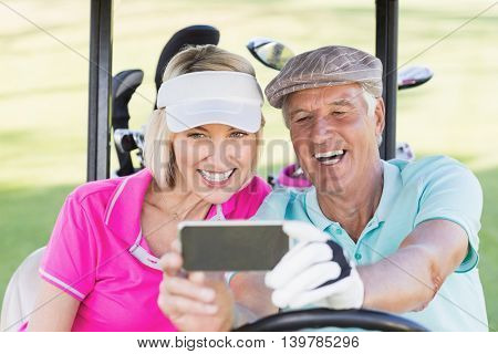 Smiling mature couple taking selfie while sitting in golf buggy