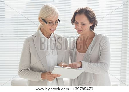 Woman with her therapist reading notes at home