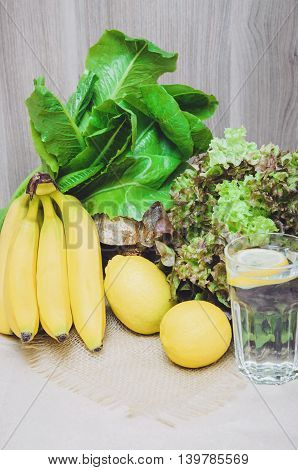 Fresh lemon water with fresh yellow lemons bananas and green plants salad. Diet healthy concept still life. Home made vitamin fortified water fruits. Lifestyle background. Copy space text place.