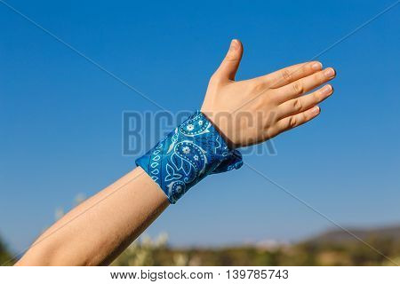 Female Hand With Blue Bandana
