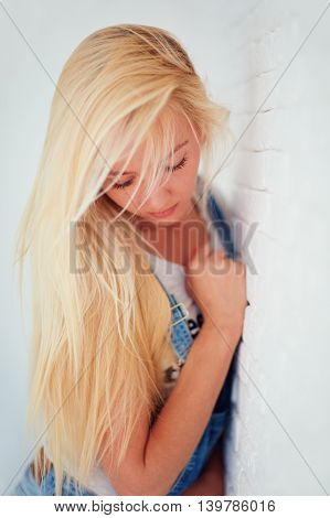 Young Girl With Blonde Hair Near The Wall