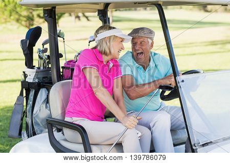 Happy mature couple sitting in golf buggy