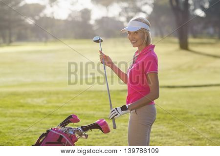 Portrait of cheerful mature woman carrying golf club while standing on field