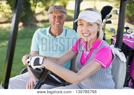 Portrait of smiling mature couple sitting in golf buggy
