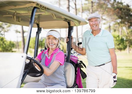 Portrait of smiling mature couple with woman sitting in golf buggy
