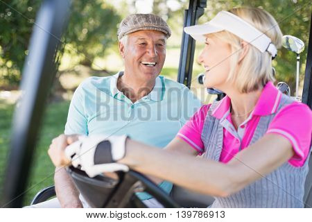 Confident mature couple sitting in golf buggy