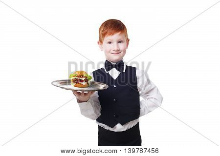 Little waiter stands with tray serving hamburger. Smiling redhead child boy in suit plays restaurant servant, gives burger isolated at white background