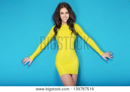 Portrait of beautiful brunette young girl with long hair. Woman posing on blue background. Summer style.