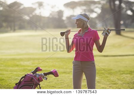 Confident mature woman carrying golf club while standing on field