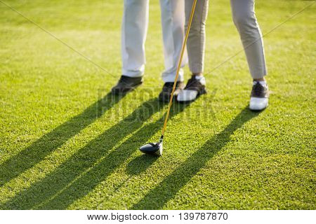 Low section of couple playing golf on grass during sunny day