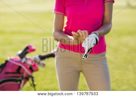 Midsection of woman wearing golf glove while standing on field