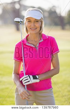 Portrait of confident mature golfer woman carrying golf club while standing on field