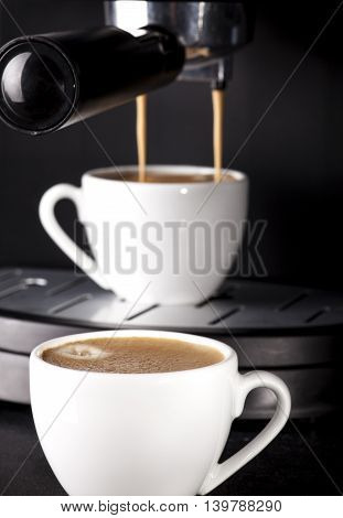 Close-up of espresso pouring from coffee machine. Two cups on black background.