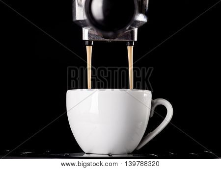 Close-up of espresso pouring from coffee machine. One cup on black background.