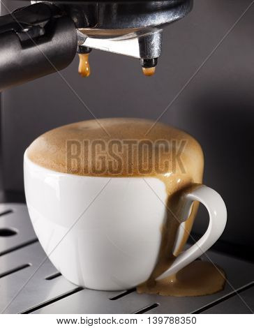 Close-up of espresso pouring from coffee machine. One cup on gray background.