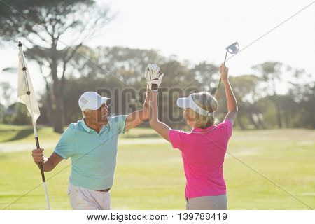Cheerful mature golfer couple giving high five while standing on field