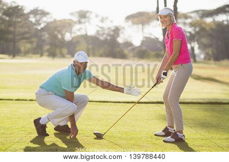 Side view of mature couple playing golf on field