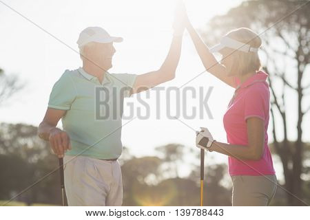 Happy golfer couple giving high five while standing on sunny day