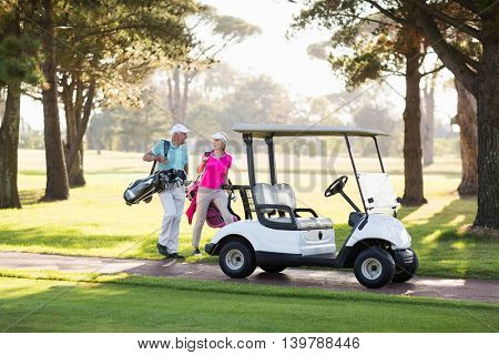 Smiling mature golfer couple by golf buggy on field