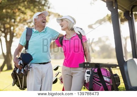Cheerful mature golfer couple with arm around while standing on field
