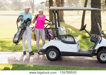 Happy mature golfer couple by golf buggy while walking on field