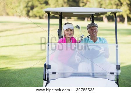 Mature golfer couple sitting in golf buggy on sunny day