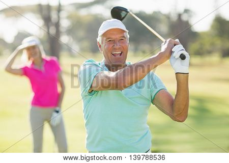 Portrait of cheerful mature golfer holding golf club while standing on field