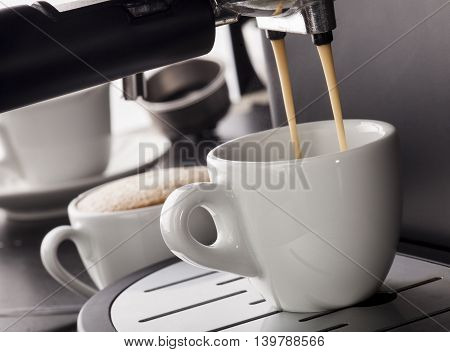 Close-up of espresso pouring from coffee machine in a white cup