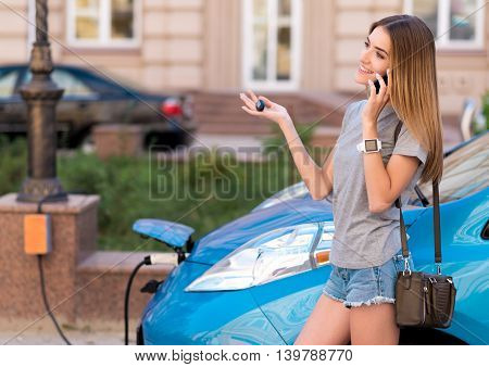 Lets meet today. Adorable young woman talking on the phone while charging her eco car in the city