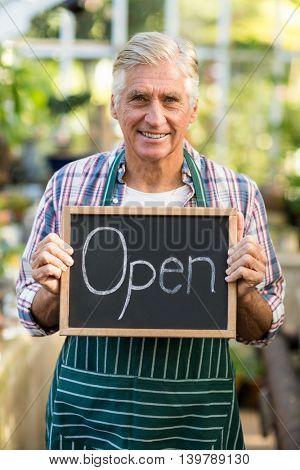 Portrait of happy mature owner holding open sign placard at greenhouse