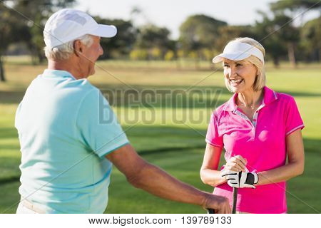 Happy mature golf player couple standing on field