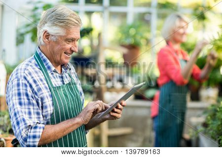 Senior man using tablet computer while wife working in background at greenhouse