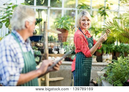 Side view of woman smiling while looking at man in greenhouse